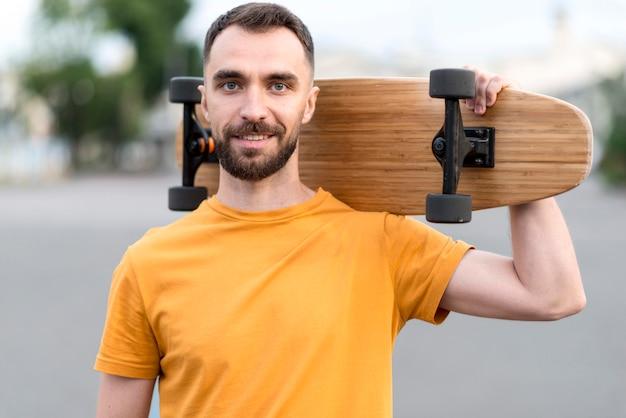 Mittlerer schuss des mannes, der ein skateboard hält