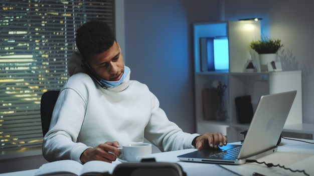 Mittlerer schuss des mannes der gemischten rasse, der am computer arbeitet, durch smartphone spricht und eine tasse tee trinkt