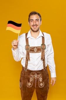 Mittlerer schuss des mannes deutsche flagge halten