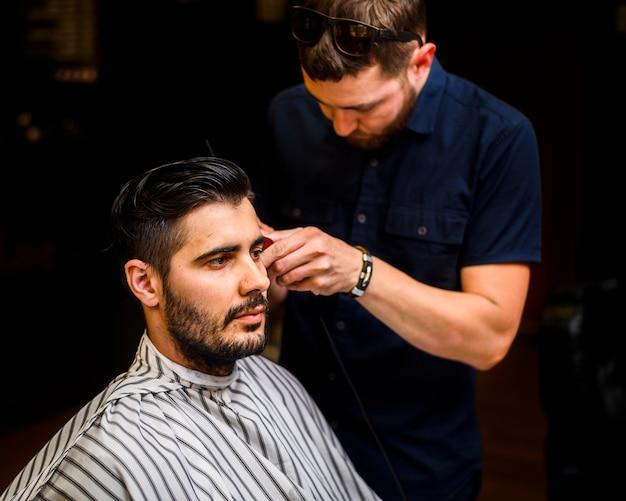 Mittlerer schuss des mannes einen haarschnitt erhalten