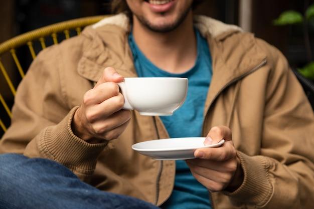 Mittlerer schuss des mannes kaffeetasse halten