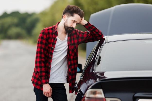 Mittlerer schuss des mannes lehnend auf auto