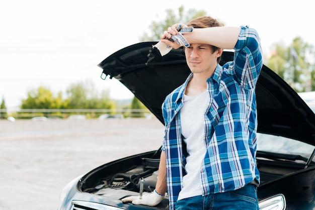 Mittlerer schuss des mannes mit auto im hintergrund