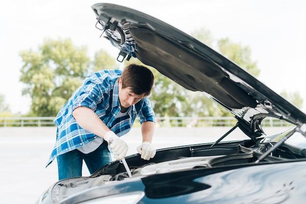 Mittlerer schuss des mannes motor reparierend