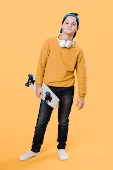 Mittlerer schuss des modernen jungen mit skateboard