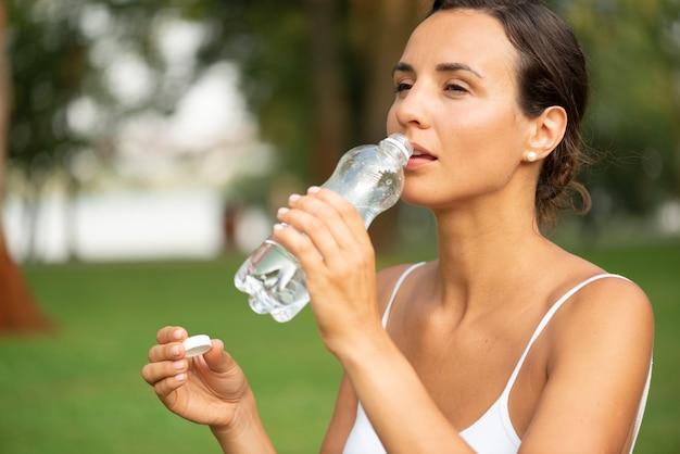 Mittlerer schuss des trinkwassers der frau