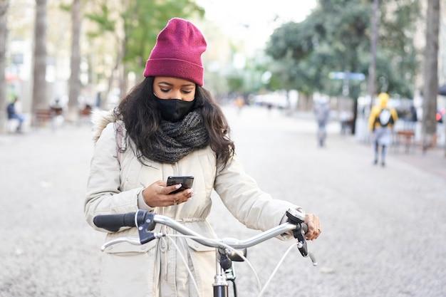 Mittlerer schuss einer jungen afroamerikanischen frau in einer stadt, die ein smartphone auf ihrem fahrrad benutzt. sie trägt winterkleidung mit schal und wollmütze.