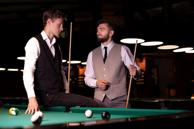 Mittlerer schuss elegante männer mit poolhinweisen