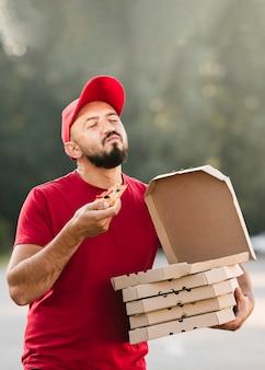 Mittlerer schuss erfüllter lieferbote, der pizza isst