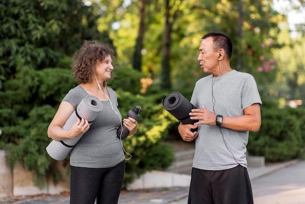 Mittlerer schuss erwachsener, der yogamatten hält