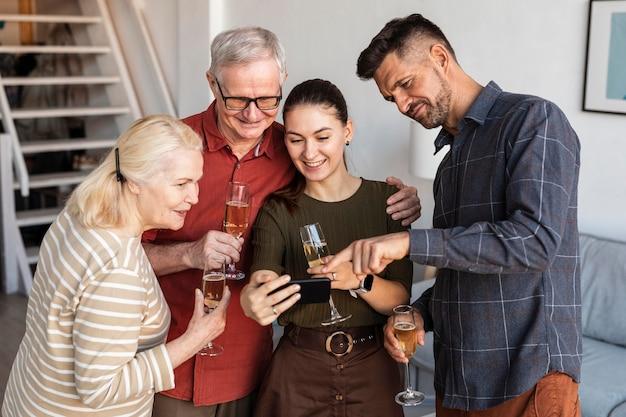 Mittlerer schuss glückliche familie, die telefon betrachtet