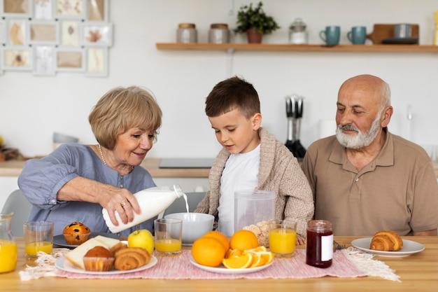 Mittlerer schuss glückliche familie, die zusammen sitzt