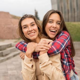 Mittlerer schuss glückliche freunde, die sich gegenseitig halten