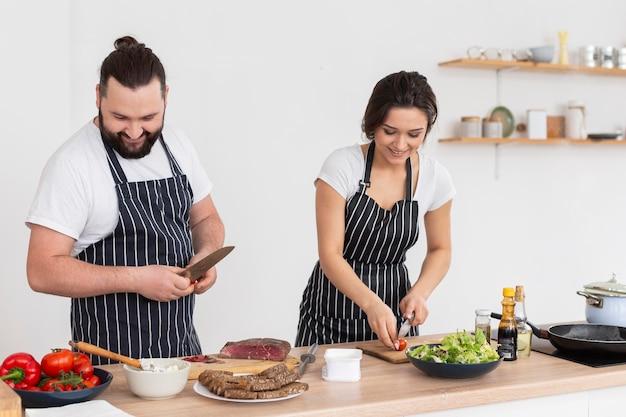 Mittlerer schuss glückliche freunde, die zusammen kochen