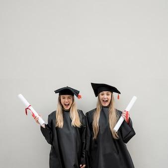 Mittlerer schuss glückliche graduierende mädchen