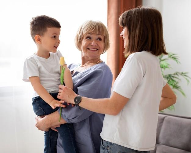 Mittlerer schuss glückliche großmutter, die kind hält