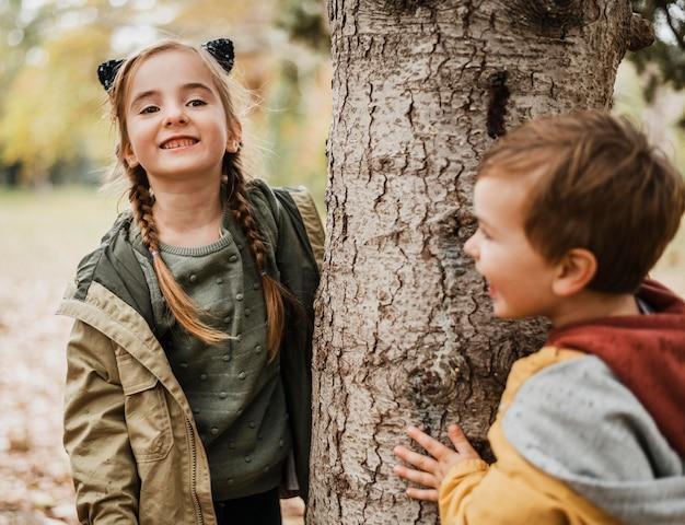 Mittlerer schuss glückliche kinder, die baum umarmen