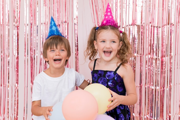 Mittlerer schuss glückliche kinder, die zusammen aufwerfen