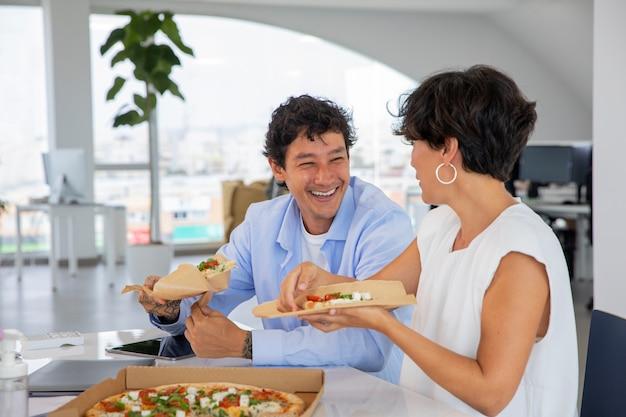 Mittlerer schuss glückliche kollegen mit pizza