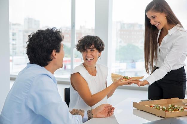 Mittlerer schuss glückliche leute mit pizza