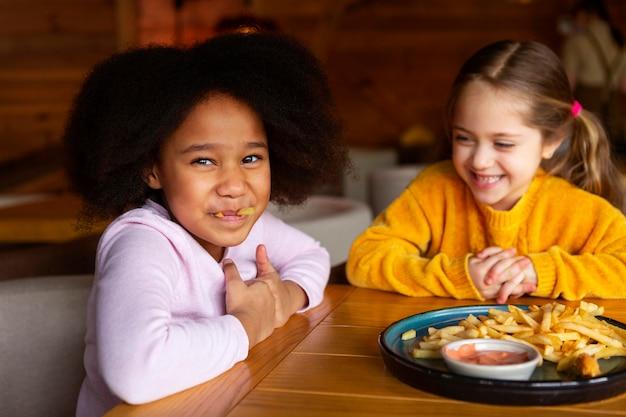 Mittlerer schuss glückliche mädchen mit essen