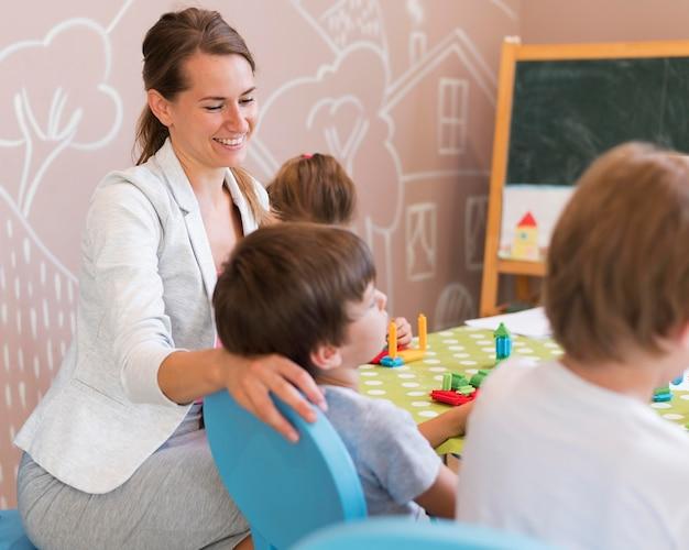 Mittlerer schuss glücklicher lehrer mit kindern