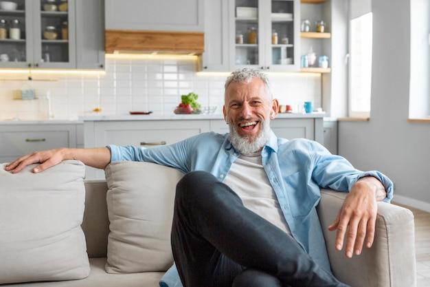 Mittlerer schuss glücklicher mann auf couch