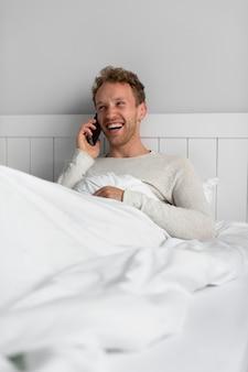 Mittlerer schuss glücklicher mann, der am telefon spricht