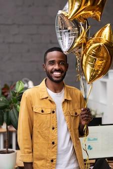 Mittlerer schuss glücklicher mann mit ballons