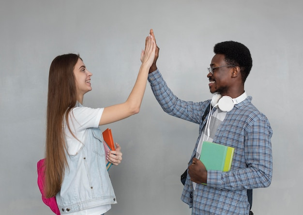 Mittlerer schuss glücklicher studenten high fiving