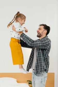Mittlerer schuss glücklicher vater, der kind hält