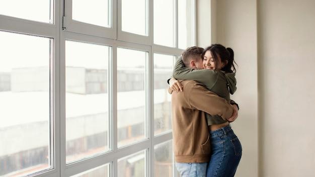 Mittlerer schuss glückliches paar, das umarmt