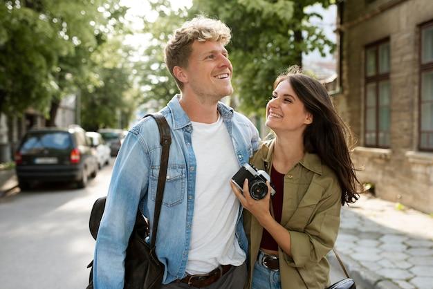 Mittlerer schuss glückliches paar mit kamera