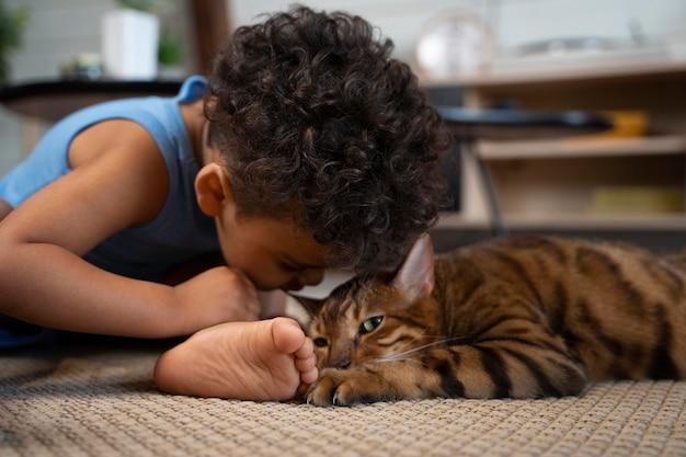 Mittlerer schuss junge, der katze anschaut