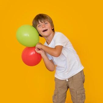 Mittlerer schuss junge, der luftballons hält