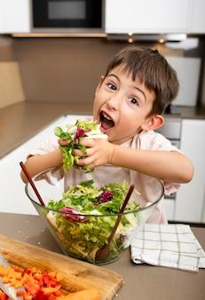 Mittlerer schuss junge, der salat hält