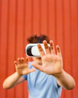 Mittlerer schuss junge, der virtual-reality-brille trägt