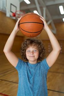 Mittlerer schuss junge hält basketball