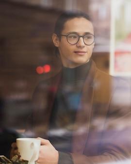 Mittlerer schuss junge mit gläsern, die tasse halten