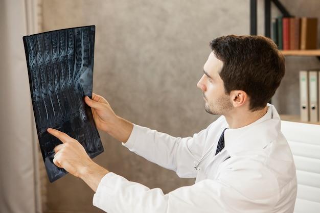 Mittlerer schuss junger arzt, der radiographie prüft