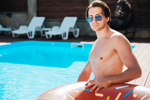 Mittlerer schuss junger mann am pool