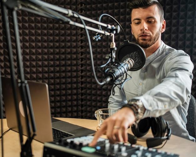 Mittlerer schuss junger mann, der am radio arbeitet