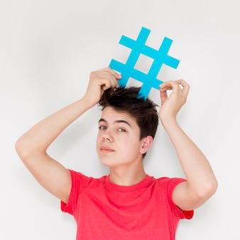 Mittlerer schuss kerl, der hashtagzeichen hält