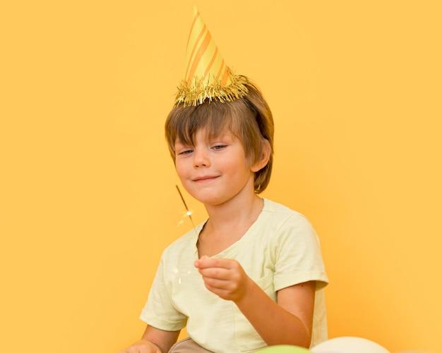 Mittlerer schuss kleiner junge, der partyhut trägt