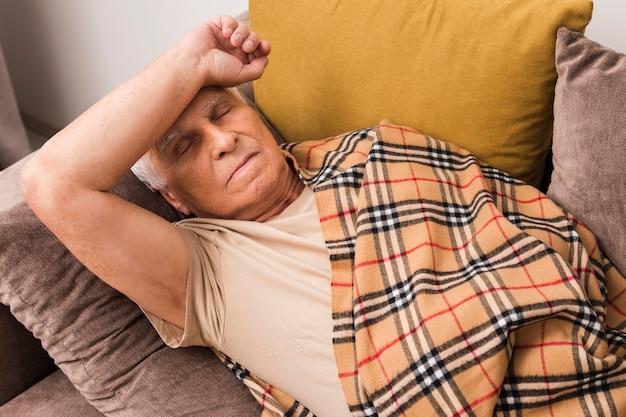 Mittlerer schuss kranker alter mann, der auf couch liegt