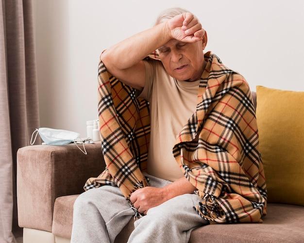 Mittlerer schuss kranker mann, der auf couch sitzt