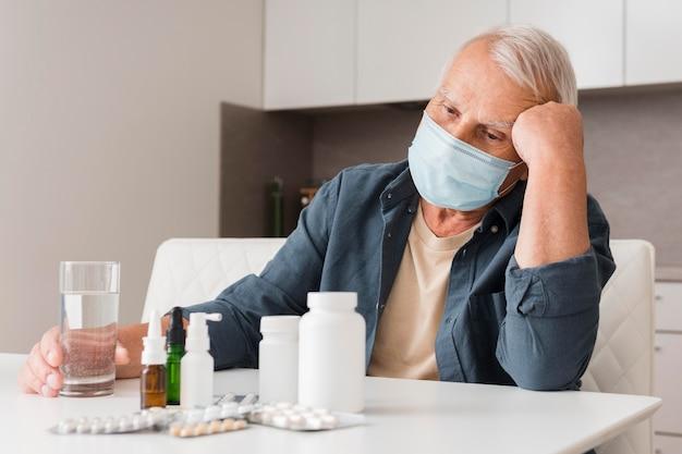 Mittlerer schuss kranker mann, der medizinische maske trägt