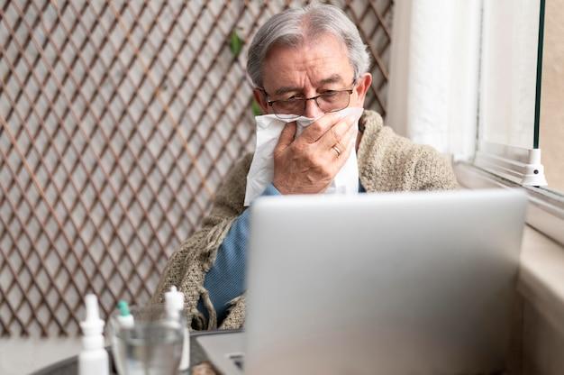 Mittlerer schuss kranker mann mit laptop