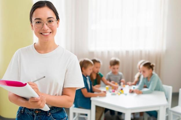 Mittlerer schuss lehrer, der notizen während des unterrichts macht