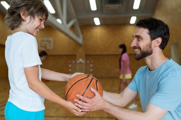 Mittlerer schuss lehrer und kind mit basketball